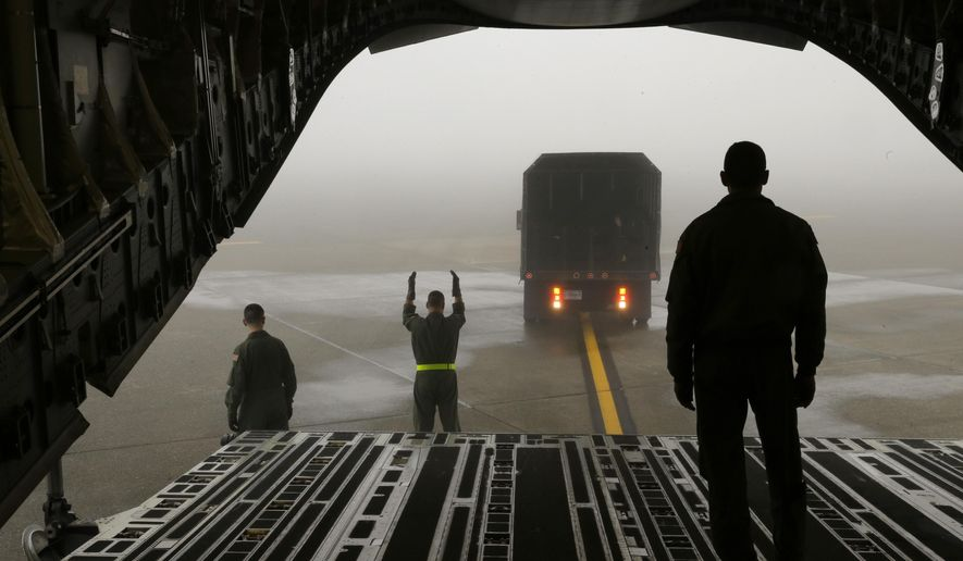Members of the Air Force Reserve 446th Aeromedical Evacuation Squadron signal as a truck backs up to unload supplies for a training fight on a C-17 cargo plane out of Joint Base Lewis-McChord, Wash., Wednesday, Jan. 21, 2015. Most medical evacuations of wounded military members are performed by Air Force Reserve and Air National Guard units. (AP Photo/Ted S. Warren)