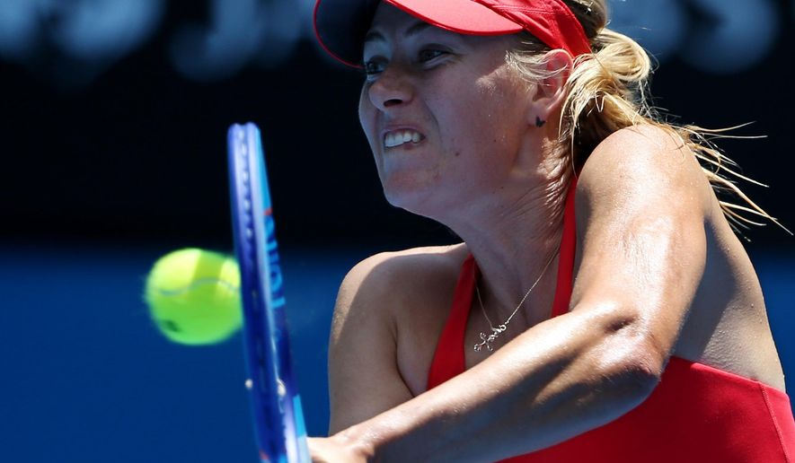 Maria Sharapova of Russia makes a backhand return to Alexandra Panova of Russia during their second round match at the Australian Open tennis championship in Melbourne, Australia, Wednesday, Jan. 21, 2015. (AP Photo/Rob Griffith)