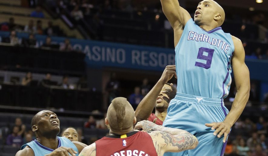 Charlotte Hornets' Gerald Henderson (9) jumps to the basket for two points over Miami Heat's Chris Andersen (11) during the first half of an NBA basketball game in Charlotte, N.C., Wednesday, Jan. 21, 2015. (AP Photo/Bob Leverone)