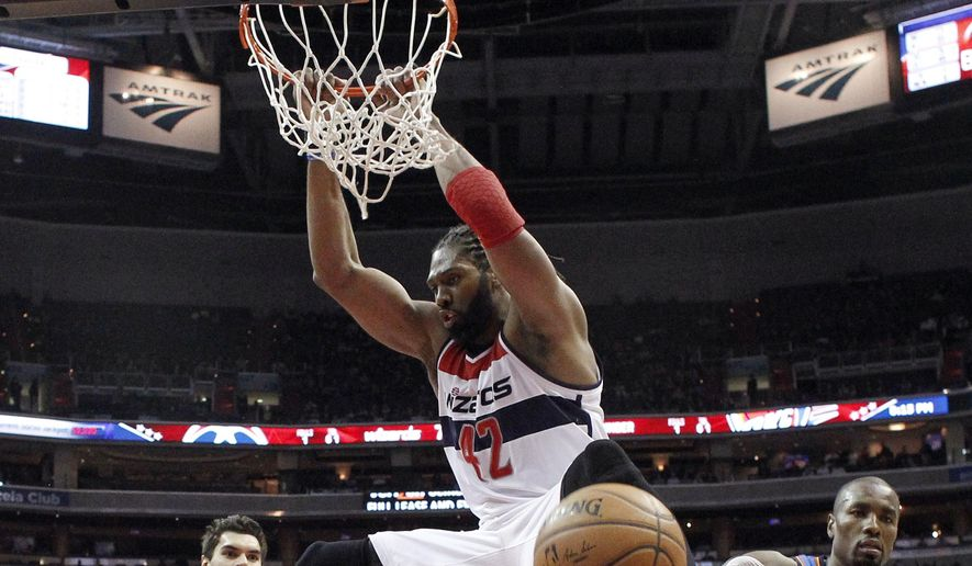 Washington Wizards forward Nene (42), from Brazil, dunks in front of Oklahoma City Thunder center Steven Adams (12), from New Zealand, and forward Serge Ibaka (9), from Congo, during the first half of an NBA basketball game, Wednesday, Jan. 21, 2015, in Washington. (AP Photo/Alex Brandon)
