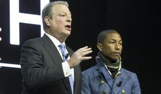"""Former US Vice President Al Gore, left, and US singer Pharrell Williams, right, attend the panel """"What's Next? A Climate for Action"""", during the World Economic Forum in Davos, Switzerland, Wednesday, Jan. 21, 2015. The meeting runs Jan. 21 through 24 under the overarching theme """"The New Global Context"""". (AP Photo/Michel Euler)"""