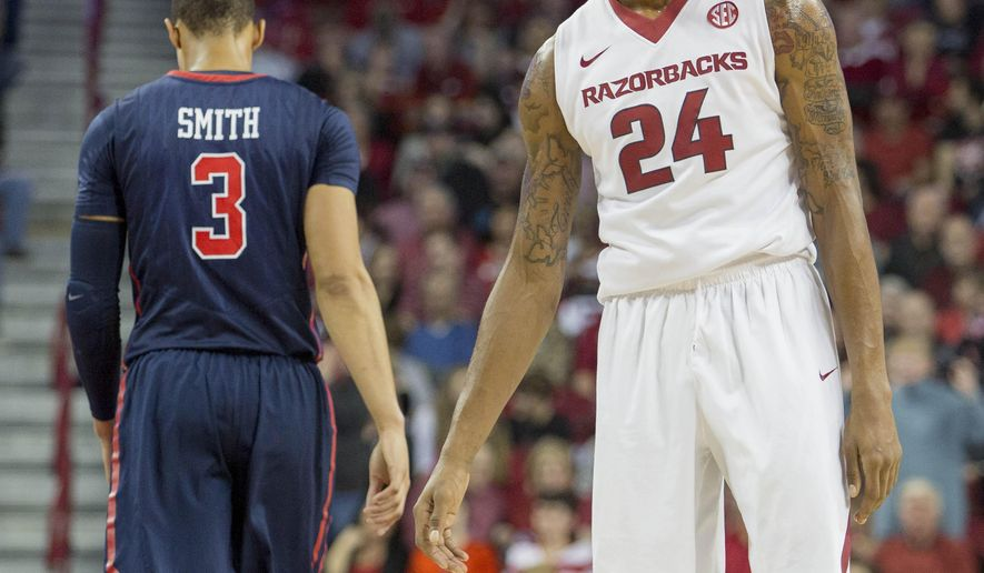 Arkansas guard Michael Qualls, right, reacts to a foul call as Mississippi guard Terence Smith, left, walks away during the first half of an NCAA college basketball game Saturday, Jan. 17, 2015, in Fayetteville, Ark. Mississippi defeated Arkansas 96-82. (AP Photo/Gareth Patterson)