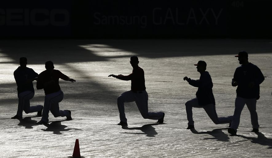 Texas Rangers players stretch on a tarp covering left field during a winter camp baseball workout Wednesday, Jan. 21, 2015, in Arlington, Texas. (AP Photo/LM Otero)