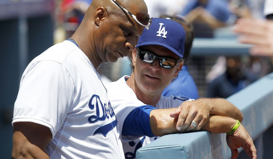 FILE - In this May 10, 2014, file photo, former Los Angeles Dodgers player Darryl Strawberry, left, talks with Dodgers manager Don Mattingly before a baseball game against the San Francisco Giants in Los Angeles. The Internal Revenue Service has auctioned off for $1.3 million the deferred compensation agreement that was part of Darryl Strawberry's 1985-90 contact with the New York Mets. St. Louis-based IRS spokesman Michael Devine says the winning bidder Tuesday, Jan. 20, 2015,  in Fairview Heights, Illinois, chose to remain anonymous. (AP Photo/Alex Gallardo, File)