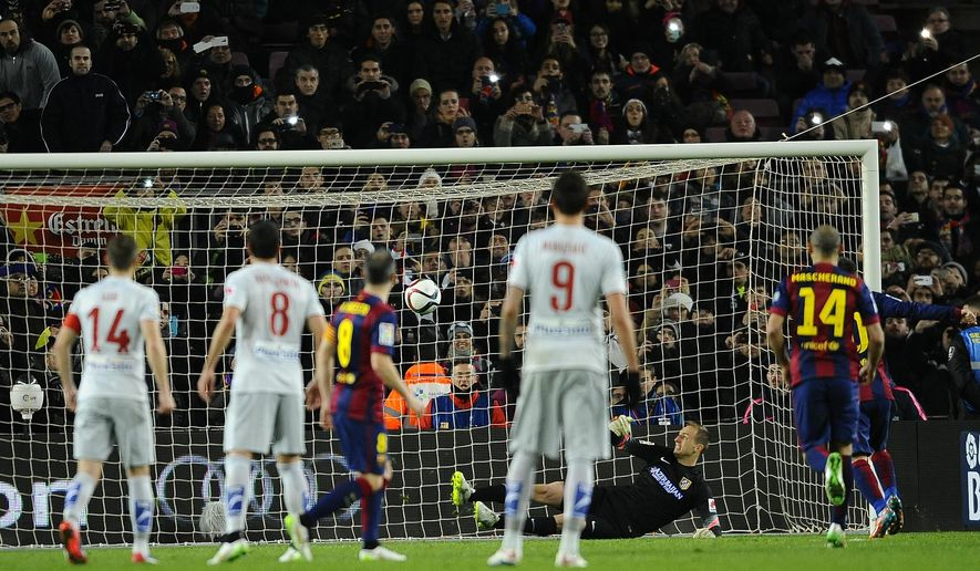 FC Barcelona's Messi, from Argentina, centre, scores a penalty against Atletico's goalkeeper Jan Oblak during a Quarterfinal Copa del Rey soccer match at the Camp Nou stadium in Barcelona, Spain, Wednesday, Jan. 21, 2015. (AP Photo/Manu Fernandez)