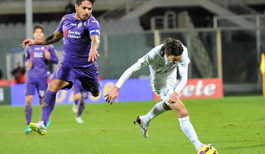 CORRECTS DATE FROM JAN. 22 TO JAN. 21 - Atalanta's Giuseppe Biava, right, and Fiorentina's Manuel Vargas vie for the ball during an Italian Cup soccer match between Fiorentina and Atalanta in Florence, Italy, Wednesday, Jan. 21, 2015. (AP Photo/Maurizio Degl'Innocenti, ANSA)