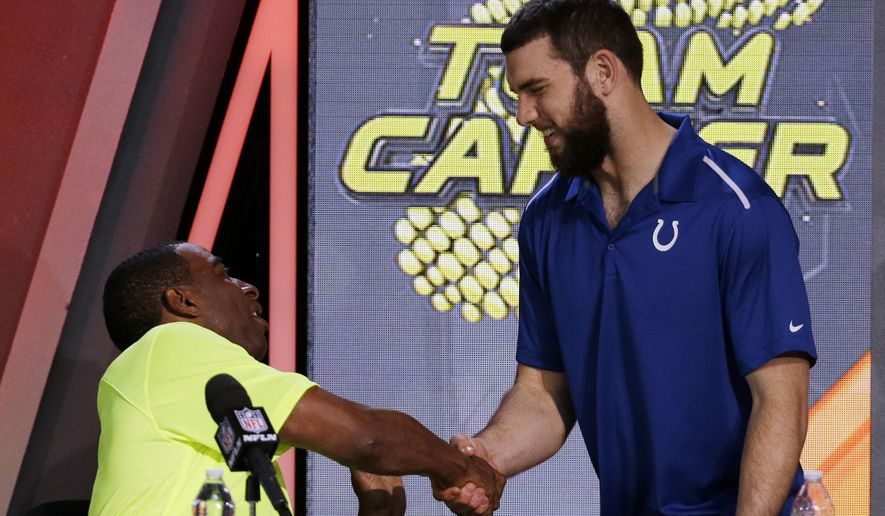 Cris Carter, left,  shakes hands with Indianapolis Colts' Andrew Luck after being picked during the Pro Bowl draft Wednesday, Jan. 21, 2015, in Phoenix. (AP Photo/David J. Phillip)