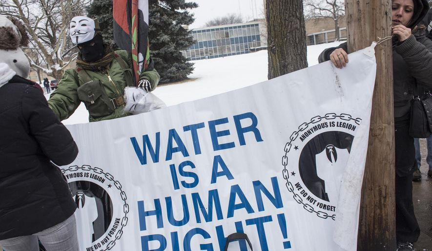 Flint resident Ashley Tucker helps hang up a banner during a protest concerning water prices and quality on Wednesday, Jan. 21, 2015, outside of City Hall in Flint, Mich. (AP Photo/The Flint Journal, Erin Kirkland) LOCAL TELEVISION OUT; LOCAL INTERNET OUT