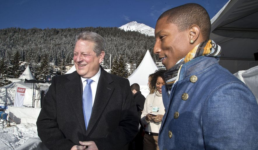 Former U.S. Vice President Al Gore, left, and U.S. singer Pharrell Williams, right, enjoy the view on the roof top of the Congress Center where the World Economic Forum takes place in Davos, Switzerland, Wednesday, Jan. 21, 2015. (AP Photo/Michel Euler) ** FILE **