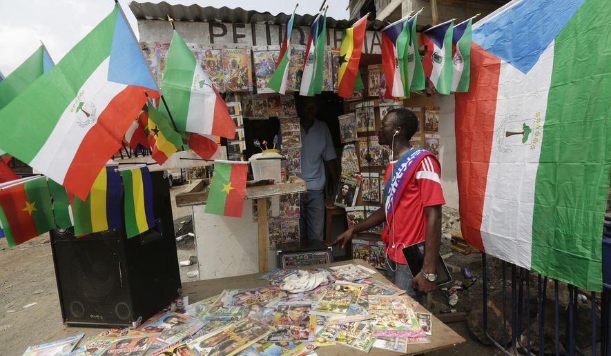 A man sells flags of different countries participating at African Cup of Nations  on the street in the neighborhood of Estadio De Malabo, Equatorial Guinea, Wednesday, Jan. 21, 2015. The African Cup of Nations soccer tournament takes place in Equatorial Guinea from Jan. 17 to Feb. 8, 2015.  (AP Photo/Sunday Alamba)