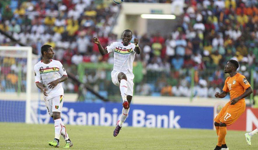 Guinea's Boubakar Fofana heads the ball watched by Ivory Coast's Serge Aurier, right, during their African Cup of Nations Group D soccer match in Estadio De Malabo in Malabo, Equatorial Guinea, Tuesday, Jan. 20, 2015. (AP Photo/Sunday Alamba)