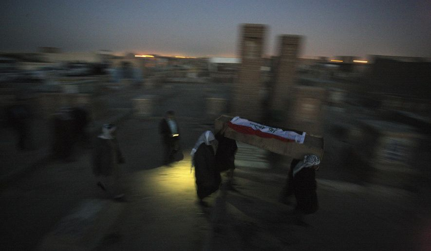 In this photo taken on Saturday, Jan. 17, 2015, mourners carry one of the coffins to bury the entire family of Khalil Abdullah during their funeral procession in the Shiite holy city of Najaf, 100 miles (160 kilometers) south of Baghdad, Iraq. Nearly six months ago Islamic State extremists kidnapped Khalil Abdullah and all his family members after the occupation of Jalula, a town in the restive Diyala province, northeast of Baghdad. Recently, Iraqi soldiers backed by Shiite militiamen retook control of Jalula and found Khalil Abdullah, his wife and their four children killed. (AP Photo/Jaber al-Helo)