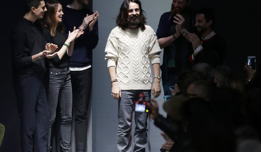 FILE - In this Monday, Jan. 19, 2015 file photo, Italian Creative Director Alessandro Michele, center, acknowledges the applause of the audience after presenting Gucci men's Fall-Winter 2015-2016 collection, part of the Milan Fashion Week, unveiled in Milan, Italy. The Gucci fashion house has named Alessandro Michele as creative director for all the brands, succeeding Frida Giannini. Michele, who was Giannini's right-hand man, led the redesign of the entire menswear line for next autumn and winter, presented Monday during Milan Fashion Week, in just five days after Giannini left Gucci earlier than anticipated. The first collection under his name will be the women's ready-to-wear for next autumn and winter, to be shown Feb. 25. Michele, 42, joined Gucci in 2002, becoming associate to the creative director in May 2011. He added the role of creative director of the Richard Ginori porcelain brand, owned by Gucci, last September. He previously worked as a senior accessories designer at Fendi and studied at the Accademia di Costume e di Moda in Rome. (AP Photo/Antonio Calanni, File)