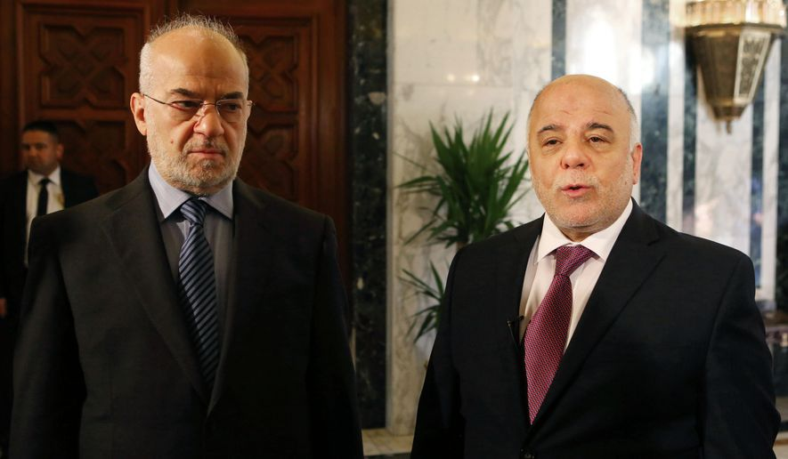 Iraq's Prime Minister Haider al-Abadi, right, stands with Iraqi Foreign Minister Ibrahim al-Jaafari at the Prime Minister's Office in Baghdad, Iraq, Wednesday, Jan. 21, 2015. Al-Abadi called on the international community to do more to help his country win the war against the Islamic State group, saying that the help pledged by a dozen countries has thus far fallen short. (AP Photo/Hadi Mizban)
