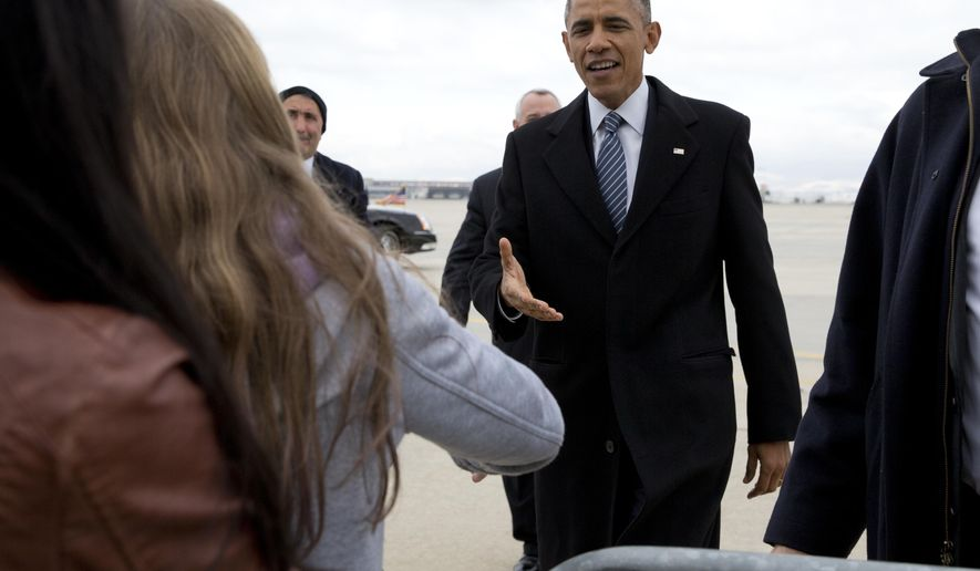 President Barack Obama greets people on the tarmac as he arrives on Air Force One at Gowen Field Air National Guard Base?, Wednesday, Jan. 21, 2015, in Boise , Idaho, en route to Boise State University where he will discuss the themes in his State of the Union address. (AP Photo/Carolyn Kaster)
