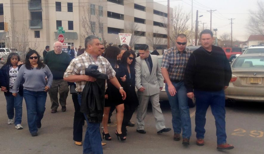 Rep. Debbie Rodella, D-Espanola, the wife of former Rio Arriba County Sheriff Thomas Rodella, center, wearing sunglasses, is helped from the federal courthouse as family members and supporters leave, on Wednesday, Jan. 21, 2015,   in Albuquerque, N.M., after the former lawman was sentenced to 10 years in federal prison in a road rage case. Rodella was convicted in September 2014 of brandishing a firearm and depriving a motorist of his rights during a March traffic stop.  (AP Photo/Russell Contreras)