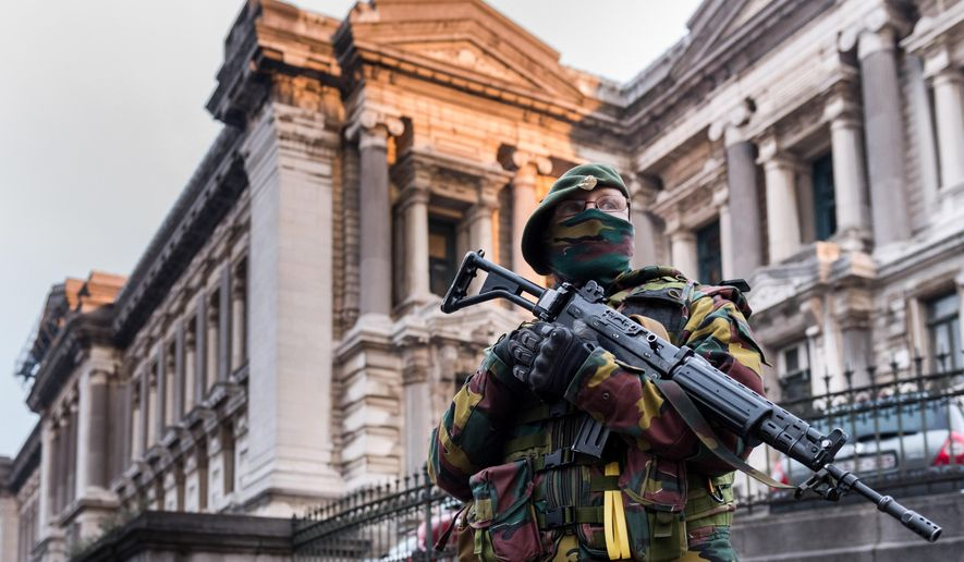 A Belgian security officer stands guard near the Palace of Justice, where suspects wanted in Belgium on terrorism-related charges are set to appear before the federal court, in Brussels on Wednesday, Jan. 21, 2015. The suspects were picked up in an anti-terror sweep following a firefight in Verviers, in which two suspected terrorists were killed. (AP Photo/Geert Vanden Wijngaert)