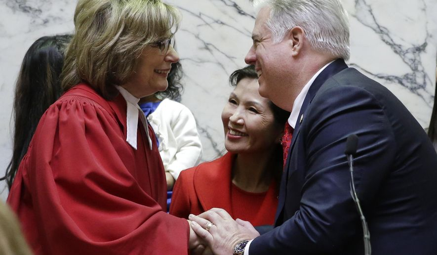 Larry Hogan, right, accompanied by his wife Yumi, shakes hands with Mary Ellen Barbera, Chief Judge of the Maryland Court of Appeals, after taking the oath of office to become the 62nd governor of Maryland inside the state senate chamber, Wednesday, Jan. 21, 2015, before an inauguration ceremony in Annapolis, Md. (AP Photo/Patrick Semansky, Pool)