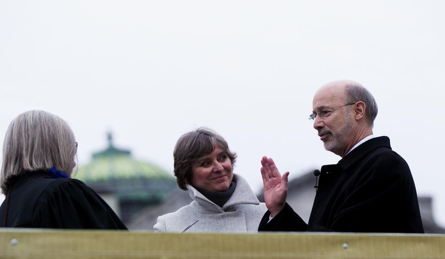 Tom Wolf, accompanied by his wife Frances, takes the oath of office from Judge Penny Blackwell to become the 47th governor of Pennsylvania Tuesday, Jan. 20, 2015, at the state Capitol in Harrisburg, Pa. (AP Photo/PennLive.com, Sean Simmers)