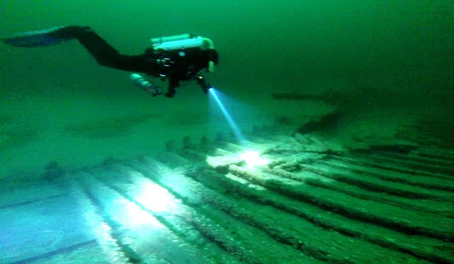 This image taken from video shows diver Andrew Driver swimming over part of a 19th-century canal boat that lies on the floor of Lake Ontario's eastern end near Oswego, N.Y. Jim Kennard, Roger Pawlowski, and Roland Steven, three underwater explorers from the Rochester area, said, Wednesday, Jan. 21, 2015, that they discovered the two 19th-century canal boats last year while searching for shipwrecks. The sunken canal boats, located in more than 200 feet below the surface, are believed to be built in the mid-1800s when the Erie Canal was widened to accommodate larger boats. (AP Photo/Bob Sherwood)