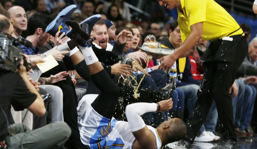 After colliding with San Antonio Spurs forward Kawhi Leonard for a loose ball, Denver Nuggets guard Randy Foye, bottom center, careens into a waiter serving drinks to fans in courtside seats in the first quarter of an NBA basketball game Tuesday, Jan. 20, 2015, in Denver. (AP Photo/David Zalubowski)