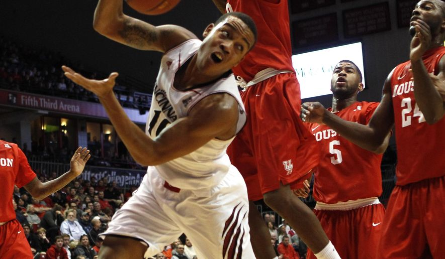 Cincinnati guard Troy Caupain (10) keeps a ball in bounds against Houston forward Danrad Knowles (0) in the first half of an NCAA college basketball game, Wednesday, Jan. 21, 2015, in Cincinnati. (AP Photo/Frank Victores)