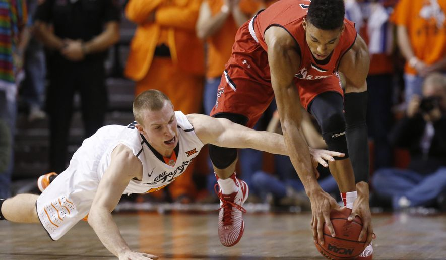 Oklahoma State guard Phil Forte, left, reaches for the ball with Texas Tech forward Justin Gray, right, in the first half of an NCAA college basketball game in Stillwater, Okla., Wednesday, Jan. 21, 2015. (AP Photo/Sue Ogrocki)