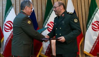 In this Tuesday, Jan. 20, 2015, photo Russia's Defense Minister Sergei Shoigu, left, and Iran's Defense Minister Hossein Dehghan exchange signed documents in Tehran, Iran. (AP Photo/ Vadim Savitsky, Russian Defense Ministry Press Service)