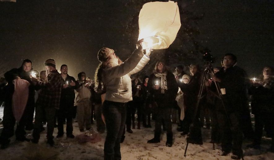 Karen Andre releases a sky lantern during the candlelight vigil at the Browns Mills United Methodist Church for a newborn baby that was set on fire, in Browns Mills, N.J., Wednesday, Jan. 21, 2015. Police found Hyphernkemberly Dorvilier's baby in flames Friday night in the middle of a Pemberton Township road and arrested her. The baby was alive and breathing when she was flown to a hospital in Philadelphia, but she died two hours later. (AP Photo/The Philadelphia Inquirer, Elizabeth Robertson)  PHIX OUT; TV OUT; MAGS OUT; NEWARK OUT