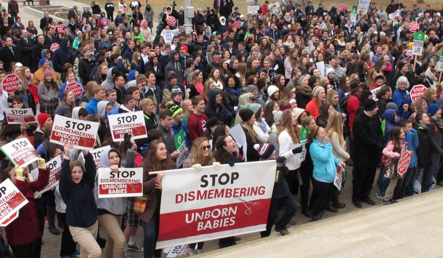 Hundreds of abortion opponents rally at the Kansas Statehouse, Thursday, Jan. 22, 2015, in Topeka, Kan. The rally was sponsored by Kansans for Life and marked the 42nd anniversary of the U.S. Supreme Court decision legalizing abortion across the nation. (AP Photo/John Hanna)