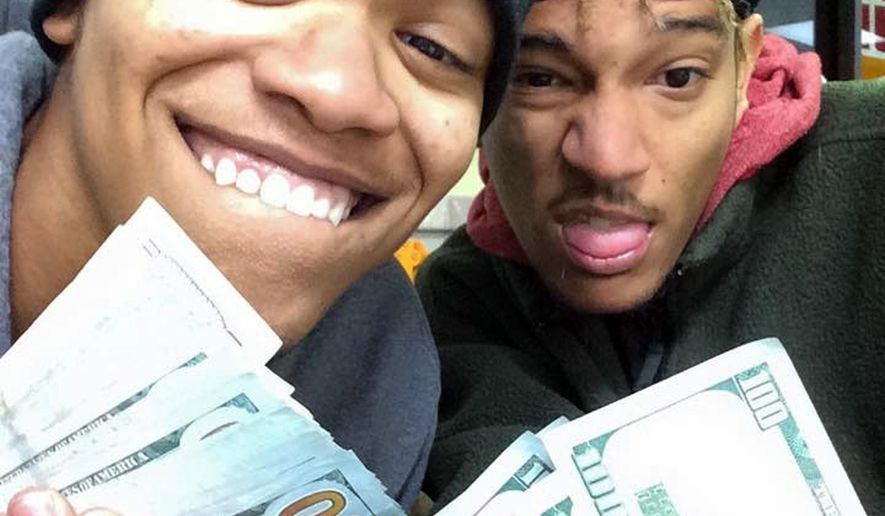 In this undated photo provided by Randy Schaefer, Dorian Walker-Gaines, left, and Dillan Thompson, pose for a selfie they unknowingly uploaded to Schaefer's iCloud account, made with Schaefer's stolen iPad holding money they allegedly took from his vehicle. Investigators arrested the pair on theft charges late Wednesday, Jan. 21, 2015, in Houston. The iPad, other electronics and thousands of dollars were stolen from the victim's truck Jan. 8. (AP Photo/Randy Schaefer)