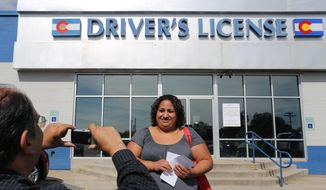 FILE - In this Aug. 1, 2014 file photo, immigrant and longtime resident in the United States Rosalva Mireles is photographed by Jesus Sanchez of Spanish language newspaper El Commercio, after Mireles was processed for her permanent driver's license, and received a temporary one to use until it is ready, at a Department of Motor Vehicles office, in Denver. Colorado Democrats are decrying a Republican decision to not add funding to a program allowing immigrants to get driver's licenses regardless of their legal status. There's been high demand for the program since it launched last year. (AP Photo/Brennan Linsley, file)