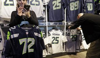 A couple of days out from the Seattle Seahawks winning the NFC championship on their way to the Super Bowl, Erin Rempel-Cheuk, left, calls her husband Tuesday, Jan. 20, 2015, in Seattle, to check on the jerseys he wants for he and his friends who will be attending the Super Bowl.   The Seahawks comeback against the Green Bay Packers Sunday sends them up against the New England Patriots in the Super Bowl in Glendale, Ariz., Feb. 1. (AP Photo/Elaine Thompson)