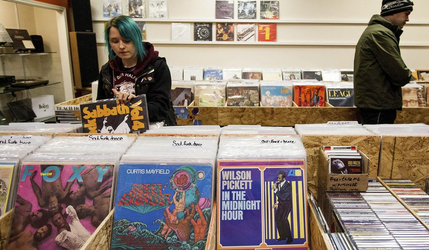 In this Jan. 15, 2015 photo, Ellie Walz, 24, digs for vinyl at the new Anchorage record store Obsession Records in Anchorage, Alaska. (AP Photo/Alaska Dispatch News, Tara Young)