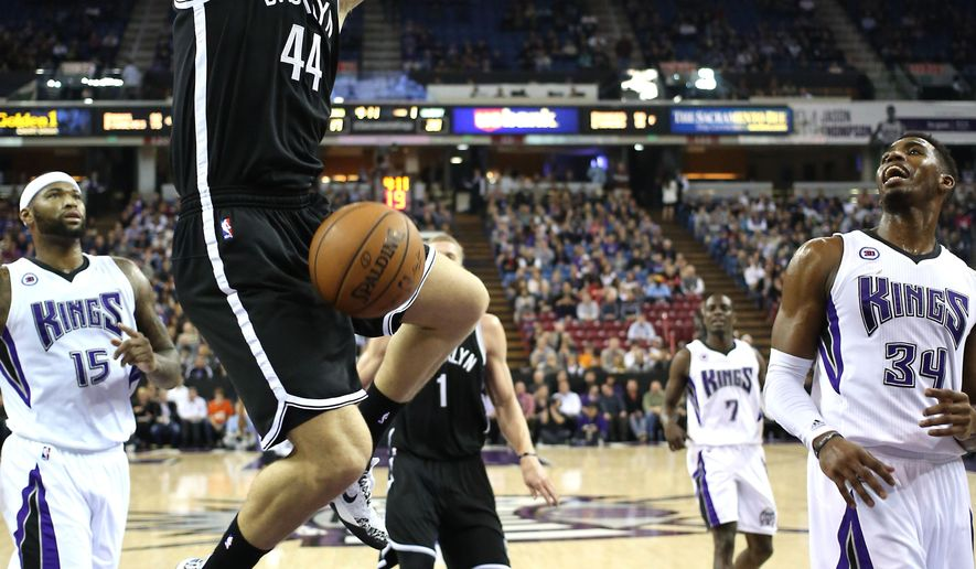 Brooklyn Nets guard Bojan Bogdanovic, center, of Croatia, goes to the basket for the stuff between Sacramento Kings' DeMarcus Cousins, left, and Jason Thompson, right, during the first quarter of an NBA basketball game in Sacramento, Calif., Wednesday Jan. 21, 2015. (AP Photo/Rich Pedroncelli)
