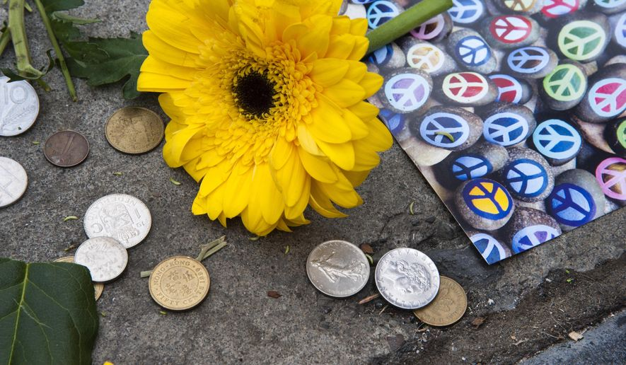 Coins, flowers and artwork are left on a sidewalk memorial for hot dog vendor Chad Rattray, on Wednesday, Jan. 21, 2015, at the corner of Riverside and Howard in Spokane, Wash.  Rattray was a fixture on the corner for the past 13 years.  He died from the flu.  (AP Photo/The Spokesman-Review, Dan Pelle)  COEUR D'ALENE PRESS OUT