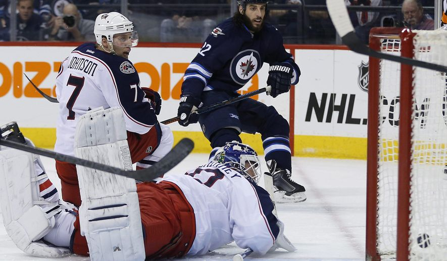 Winnipeg Jets' Chris Thorburn (22) scores on Columbus Blue Jackets goaltender Curtis McElhinney (30) as Jack Johnson (7) defends during the second period of an NHL hockey game Wednesday, Jan. 21, 2015, in Winnipeg, Manitoba. (AP Photo/The Canadian Press, Jason Woods)