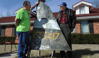 Former pilot Charles Screws, 93, right, looks for the first time in 71 years at a piece of the tail of his P-47 Thunderbolt plane, Thursday, Jan. 16, 2015, in Abilene, Texas. The plane was shot down over France in 1944.  At left is Malcolm Laing, director of the Texas Air Museum in Slaton, where the relic is going on display. (AP Photo/Abilene Reporter-News, Nellie Doneva)