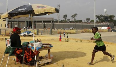 A young boy runs next to a woman selling food outside the stadium during the African Cup of Nations Group B soccer match between Tunisia and Zambia in Ebibeyin, Equatorial Guinea, Thursday, Jan. 22, 2015. (AP Photo/Themba Hadebe)