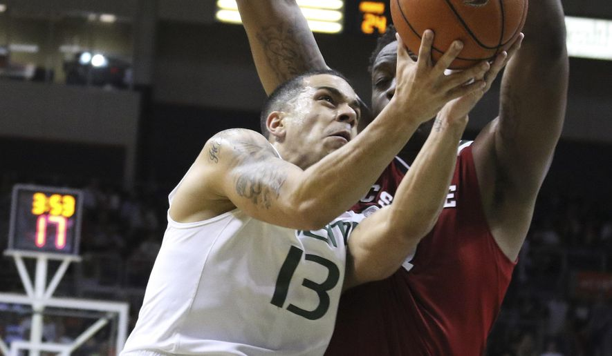 Miami's Angel Rodriguez (13) and North Carolina State's BeeJay Anya battle for the ball during the first half of an NCAA college basketball game in Coral Gables, Fla., Thursday, Jan. 22, 2015. (AP Photo/J Pat Carter)