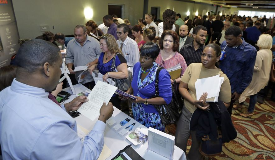 In this photo taken Wednesday, Oct. 22, 2014, Russell Neal, left, gives job information to job seeker Queena Moise, foreground second from right, at a job fair in Miami Lakes, Fla. The U.S. Labor Department reports on the number of people who applied for unemployment benefits the week ending Jan. 17, 2015 on Thursday, Jan. 22, 2015. (AP Photo/Alan Diaz) **FILE**