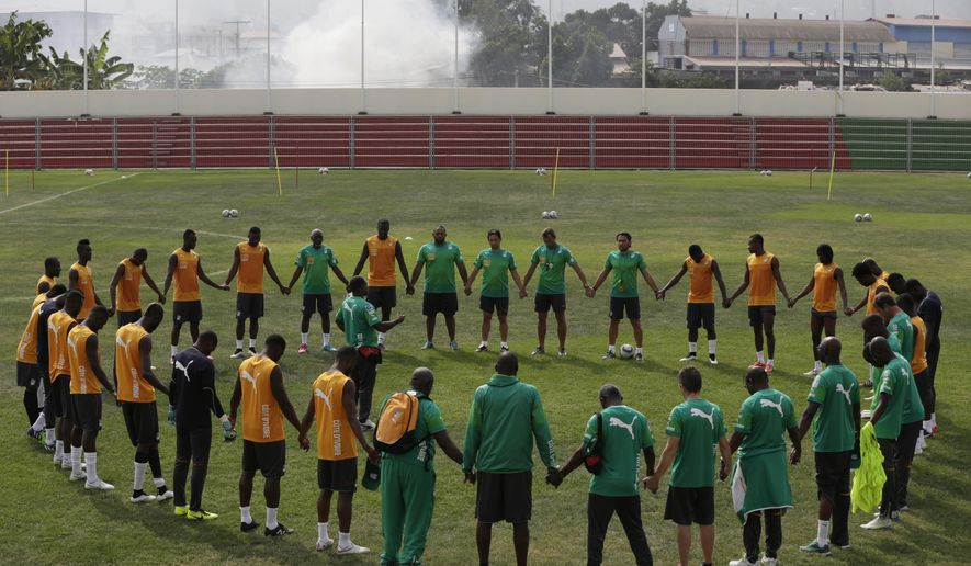Ivory Coast players and team staff join hands in a circle at the start of a training session at La Paz Stadium at  La Paz Stadium in Malabo, Equatorial Guinea, Thursday, Jan. 22, 2015. (AP Photo/Sunday Alamba)