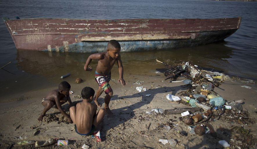 In this Tuesday, Jan. 20, 2015 photo, boys play next to an abandoned boat, on the garbage-littered shore of Guanabara Bay in Rio de Janeiro, Brazil. Rio de Janeiro state's top environmental official acknowledged at a Friday, Jan. 23rd press conference, that the Olympic pledge of slashing by 80 percent the levels of pollution flowing into the trash- and raw sewage-filled Guanabara Bay is unattainable by next year's summer games. (AP Photo/Leo Correa)