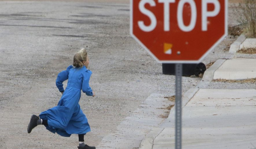 In this Dec. 16, 2014, photo, a girl runs past a street sign in Hildale, Utah. The sister cities of Hildale and Colorado City, Ariz., once run by polygamist leader Warren Jeffs, are split between loyalists who still believe he is a victim of religious persecution and defectors who are embracing government efforts to pull the town into modern society. (AP Photo/Rick Bowmer)