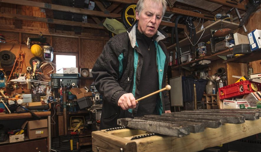 """ADVANCED FOR RELEASE SUNDAY, JANUARY 25, 2015 Tom Kaufmann plays one of his """"lithophone"""" musical instrument in his workshop in Traverse City, Mich. (AP Photo/Traverse City Record-Eagle, Pete Rodman)"""
