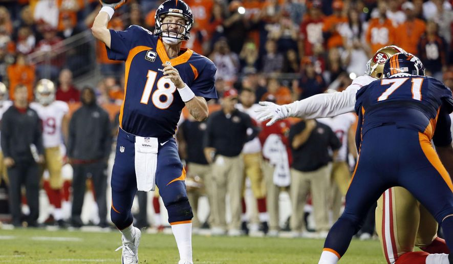 FILE - In this Oct. 19, 2014, file photo, Denver Broncos quarterback Peyton Manning throws his 509th career touchdown pass, breaking Brett Favre's mark, to set the NFL record, during a football game against the San Francisco 49ers in Denver. (AP Photo/Jack Dempsey, File)