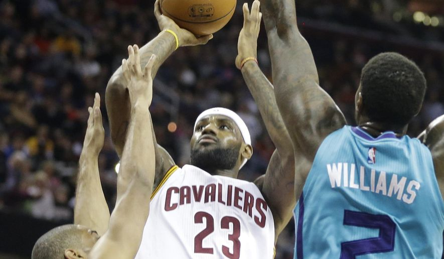 Cleveland Cavaliers' LeBron James (23) shoots over Charlotte Hornets' Gary Neal, left, and Marvin Williams (2) in the first quarter of an NBA basketball game Friday, Jan. 23, 2015, in Cleveland. (AP Photo/Mark Duncan)