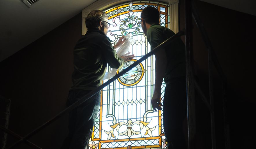 Kevin Grabowski, left, and Brandon Geppi of Conrad Schmitt Studios install a stained glass window in the governor's mansion in Pierre, S.D. on Friday, Jan. 23, 2015.  The window was a gift from Conrad Schmitt Studios, which performed the Capitol work. The $3 million Capitol restoration involved refurbishing stained glass in the Capitol rotunda, above the grand staircase and over the House and Senate chambers. (AP Photo/James Nord)