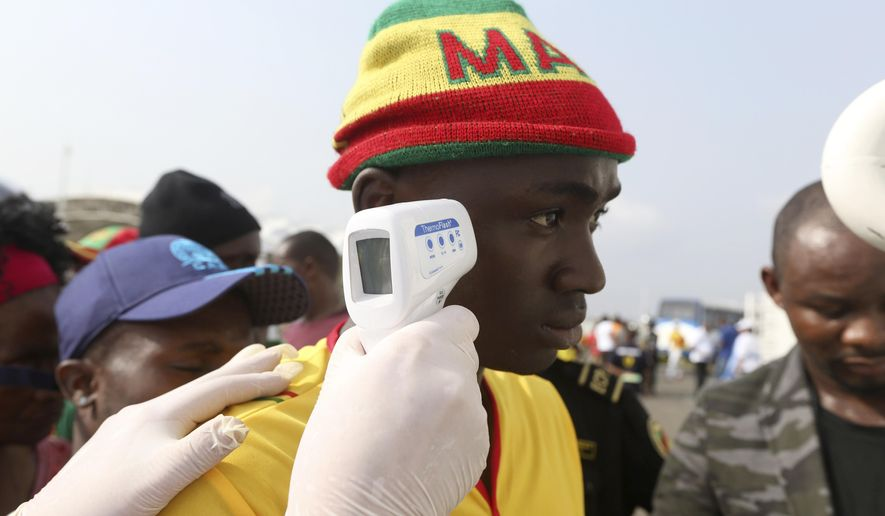 A health official takes the temperature of a Malian soccer fan for Ebola Virus ahead of the African Cup of Nations Group D soccer match between Ivory Coast and Guinea at the Estadio de Malabo in Malabo, Equatorial Guinea, Tuesday, Jan. 20, 2015. (AP Photo/Sunday Alamba)