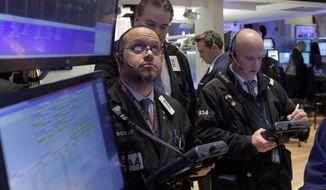 Trader Robert Arciero, left, works on the floor of the New York Stock Exchange Friday, Jan. 23, 2015.  (AP Photo/Richard Drew) ** FILE **